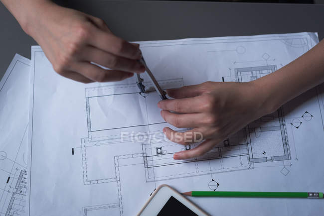 Close-up of female executive working on blueprint in office — Stock Photo