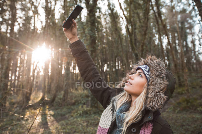 Blonde woman taking selfie with mobile phone in forest. — Stock Photo