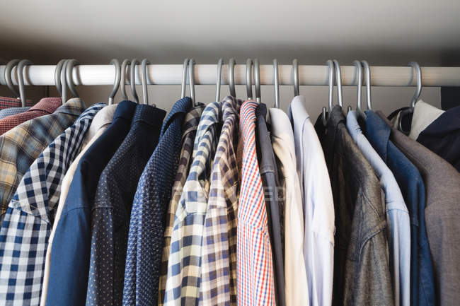 Close-up of various shirts hanging in hangers at home — Stock Photo
