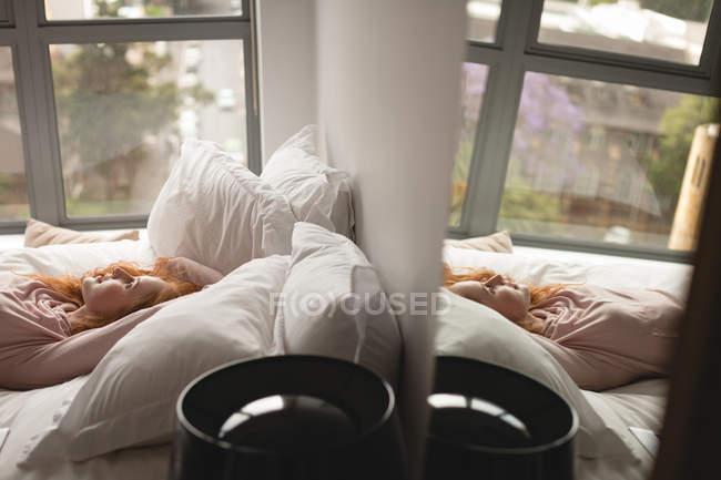 Жінка розслабляючий на ліжку в спальні в домашніх умовах — стокове фото