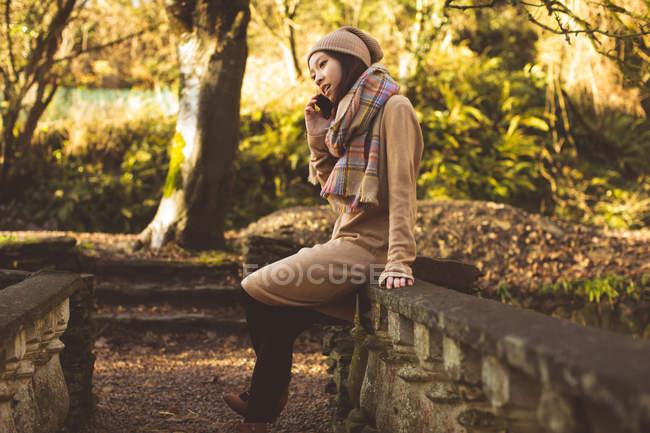 Женщина разговаривает по мобильному телефону в лесу — стоковое фото
