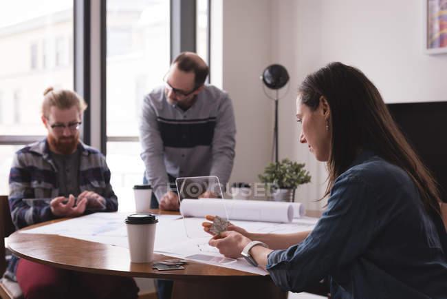 Женский исполнитель, с помощью мобильного телефона стекла в интерьер офиса с мужчинами, работающих в фоновом режиме — стоковое фото