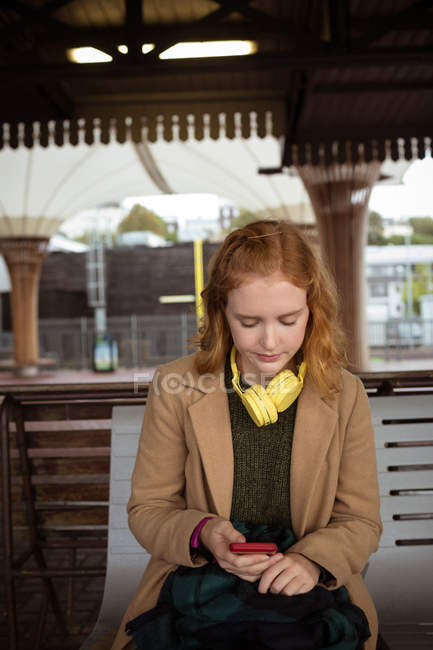 Young woman using her mobile phone at railway station — Stock Photo