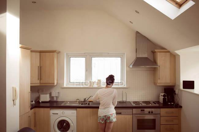 Задній вид жінки, що працюють в інтер'єрі кухні в домашніх умовах. — стокове фото
