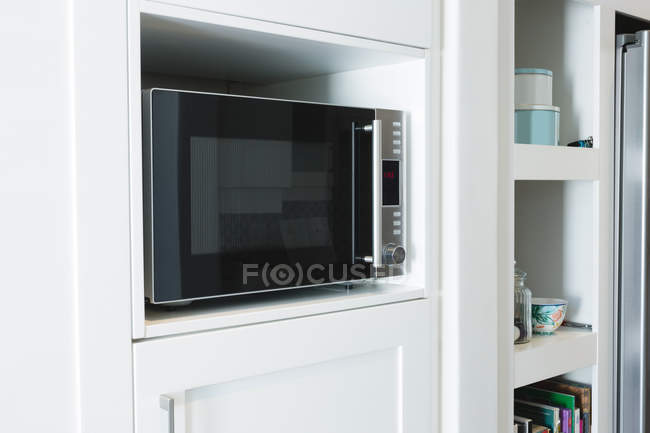 Gros plan du four à micro-ondes dans l'armoire à la maison — Photo de stock