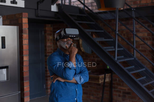 Старший чоловік на дому за допомогою віртуальної реальності гарнітура — стокове фото