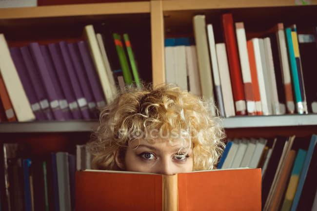 Portrait de jeune femme cachant son visage derrière un livre à la bibliothèque — Photo de stock