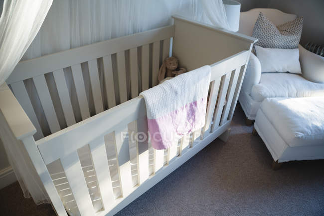 Wooden cradle with soft toy at home — Stock Photo