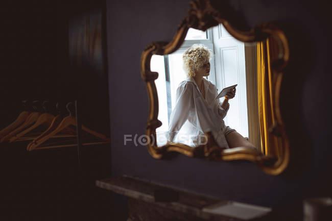 Reflexo da mulher usando tablet digital perto de janela no espelho em casa — Fotografia de Stock