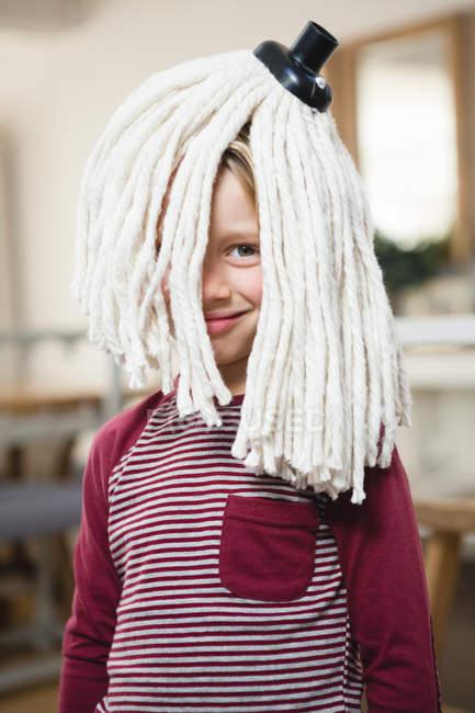 Счастливый мальчик со шваброй на голове на кухне дома — стоковое фото