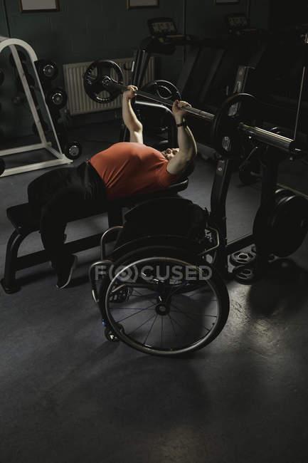 Hombre discapacitado haciendo ejercicio en el pecho en press de banca con barra en el gimnasio - foto de stock