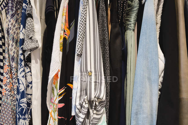 Close-up of various female clothes hanging in hangers at home — Stock Photo