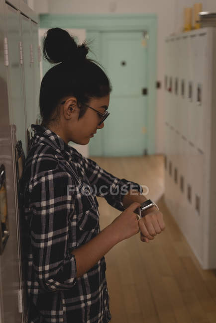 Female executive using smartwatch in locker room at creative office — Stock Photo