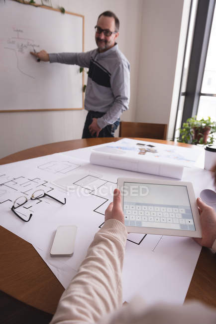 Male executive discussing chart on whiteboard with female coworker in office — Stock Photo