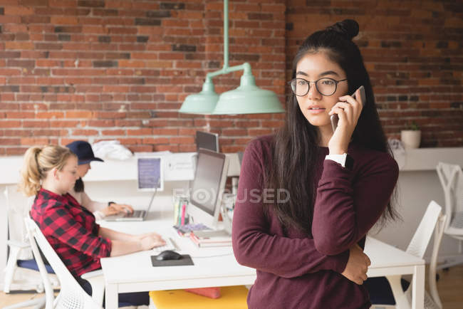 Female executive talking on mobile phone while colleagues working in background at office — Stock Photo