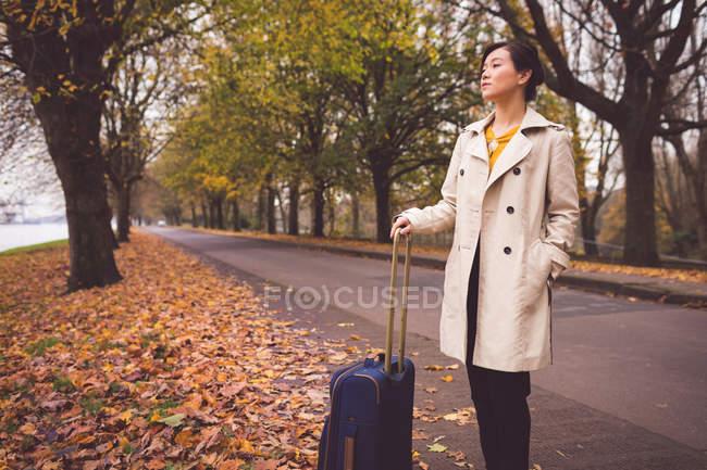 Geschäftsfrau mit Gepäck steht im Herbst auf der Straße — Stockfoto