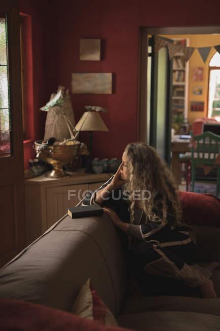 Nachdenklich Reife Frau sitzt auf dem Sofa zu Hause — Stockfoto