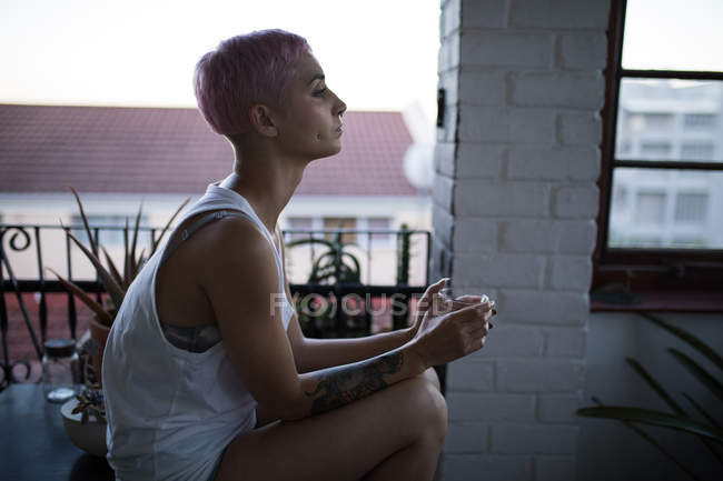 Side view of woman in thoughtful mood sitting at home. — Stock Photo