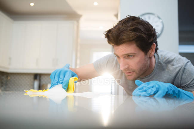 Young man cleaning kitchen worktop at home — Stock Photo