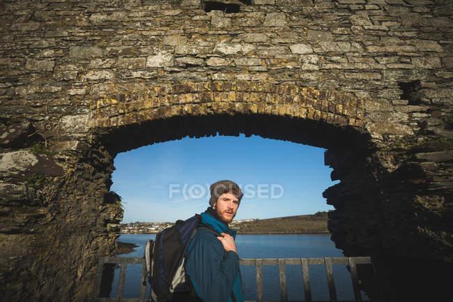 Молодой турист-мужчина стоит в старых руинах в сельской местности — стоковое фото