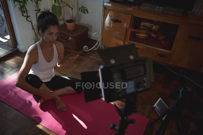 Female video blogger on yoga mat recording vlog at home — Stock Photo