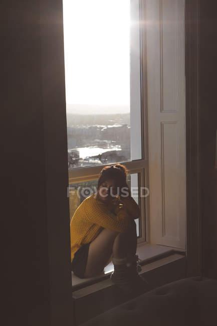 Mulher atenciosa relaxando perto da janela em casa — Fotografia de Stock