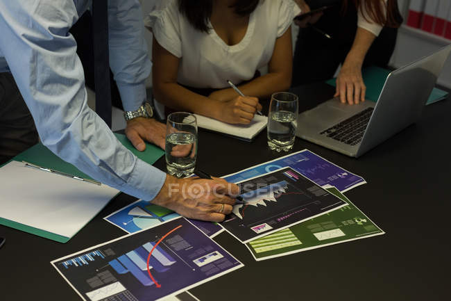 Business colleagues discussing over graph document in office — Stock Photo