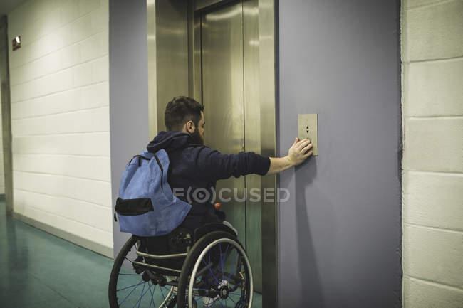 Hombre discapacitado pulsando botón de ascensor en el edificio - foto de stock