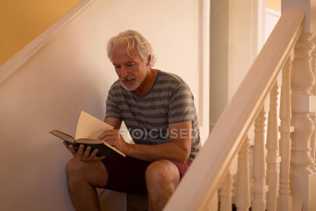 Aktive senior Mann liest ein Buch über die Treppe zu Hause — Stockfoto