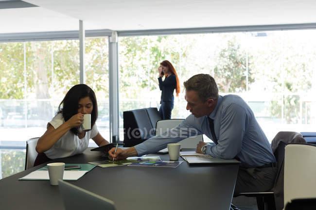 Colleghi d'affari che discutono su documenti in carica — Foto stock