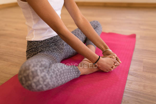 Low section of woman performing yoga exercise in fitness club — Stock Photo