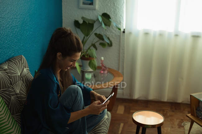 Femme utilisant un téléphone portable sur le canapé dans le salon à la maison — Photo de stock