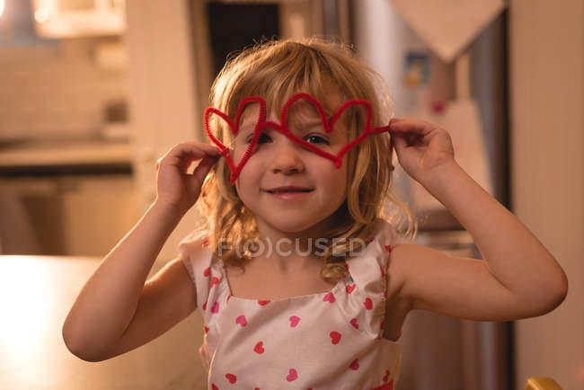 Menina segurando a decoração de forma de coração em casa — Fotografia de Stock