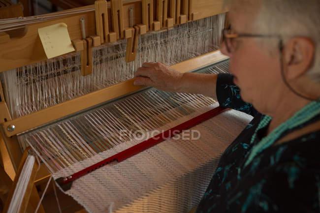 Active senior woman weaving silk at shop — Stock Photo