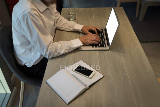 Milieu de section de l'homme d'affaires en utilisant un ordinateur portable au bureau dans la chambre d'hôtel — Photo de stock