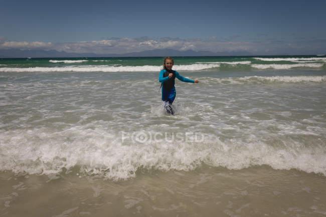 Happy girl running in sea at beach — Stock Photo