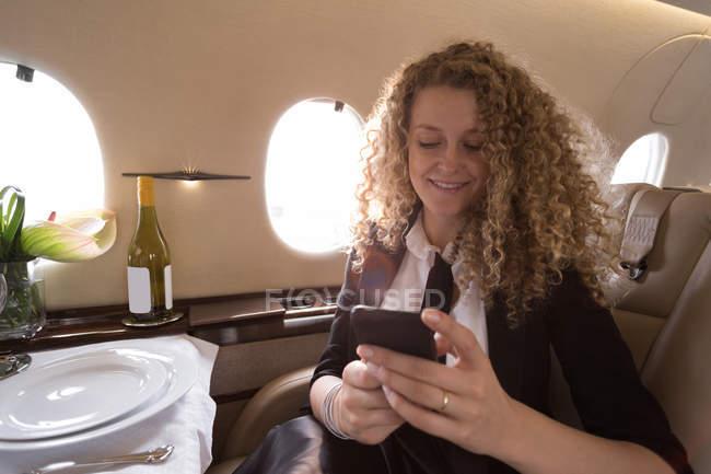 Femme d'affaires blonde utilisant un téléphone mobile en jet privé — Photo de stock