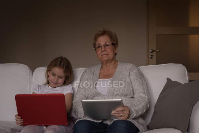 Grand-mère et petite-fille utilisant ordinateur portable et tablette numérique à la maison — Photo de stock