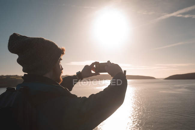 Male hiker taking photo with mobile phone near lake at countryside — Stock Photo