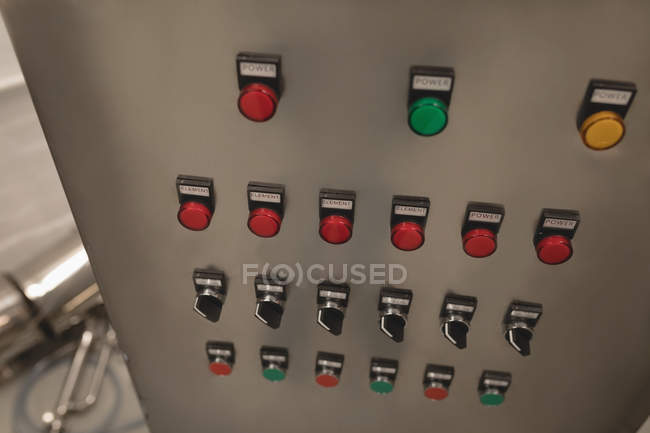 Red, green and yellow buttons on machine in factory — Stock Photo