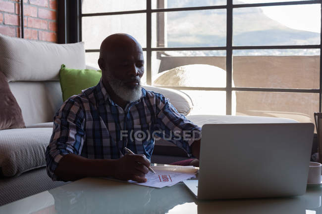 Senior man checking invoices while using laptop at home — Stock Photo