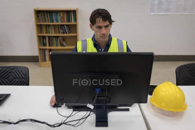 Lavoratore di sesso maschile che lavora al computer presso l'ufficio della stazione solare — Foto stock