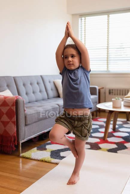 Девочка, занимающаяся йогой в гостиной дома — стоковое фото