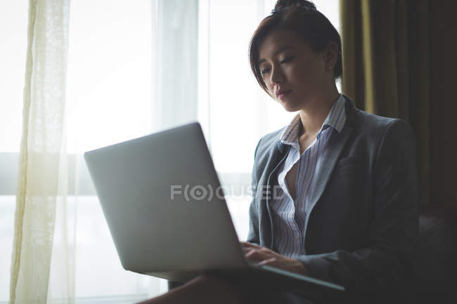 Businesswoman using laptop while sitting on arm chair in hotel room — Stock Photo