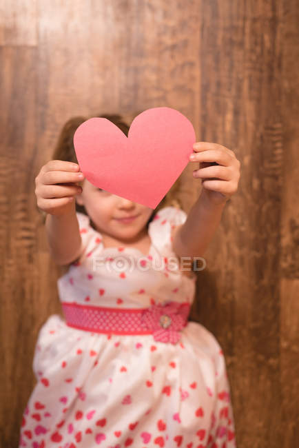 Girl holding heart shape decoration — Stock Photo