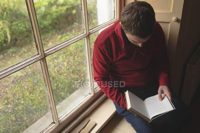 Mann liest ein Buch in der Nähe von Fenster zu Hause — Stockfoto