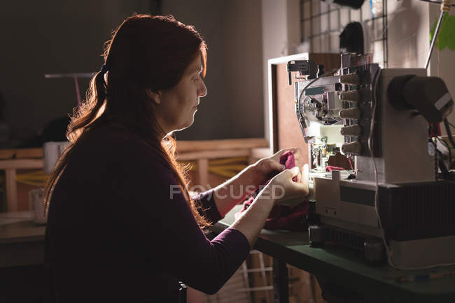 Tailor sewing cloth with sewing machine at tailor shop — Stock Photo