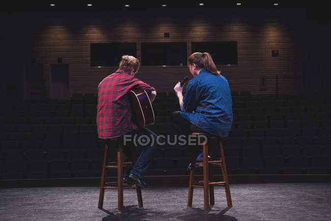 Singer and musician performing on stage at theatre. — Stock Photo