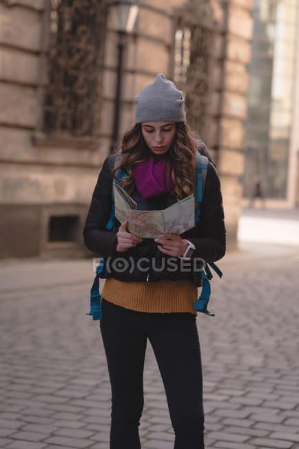 Junge Frau auf der Suche auf Karte auf Straße — Stockfoto