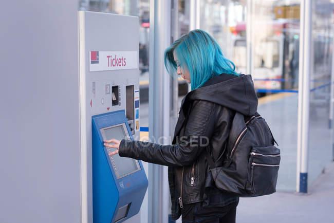 Стильною жінкою, використовуючи автомат квиток на вокзалі — стокове фото